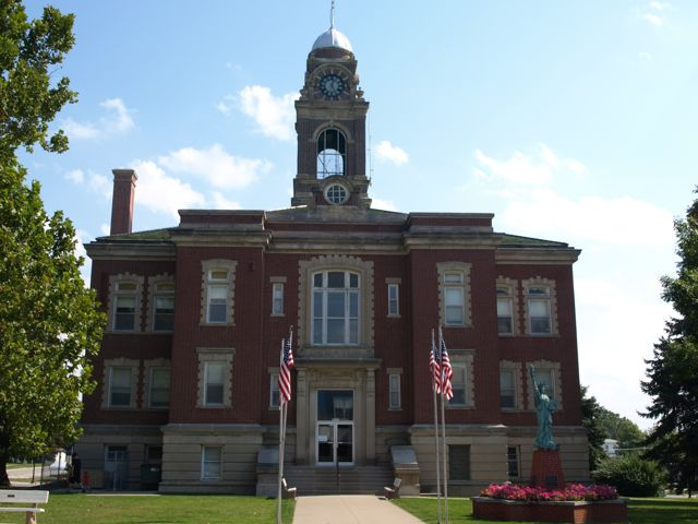 front of courthouse, with flags and replica of the Statue of Liberty