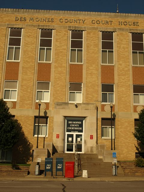 "Closer view of east entrance. Shows steps to door, and raised text near top of building ""Des Moines County Court House"""
