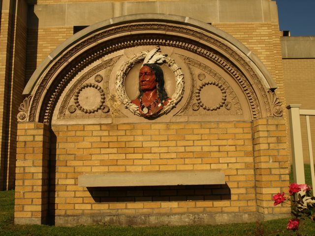 Momument with stone carvings on east lawn, shows Indian bust. From previous courthouse