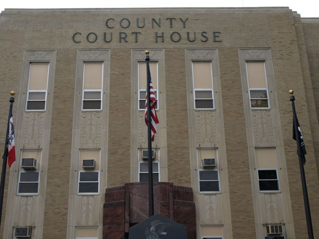"Close view of the front of the courthouse. Text ""County Court House"" in dark raised letters above the third floor"