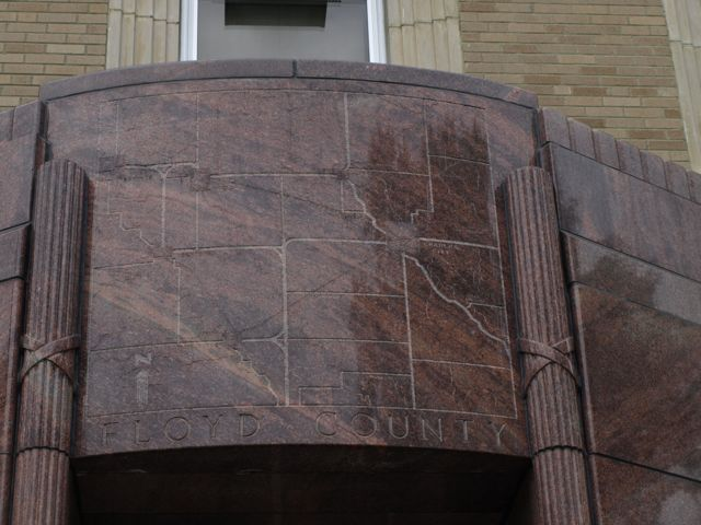 Close view of the dark polished granite above the door. A map of Floyd County is etched in the stone