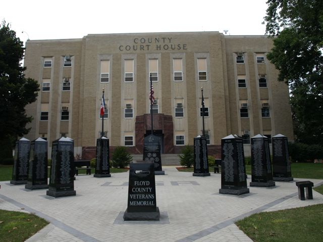 A wide view of the Floyed County Veterans Memorial. Several tall obelisks line a brick courtyard. The courthouse is in the background