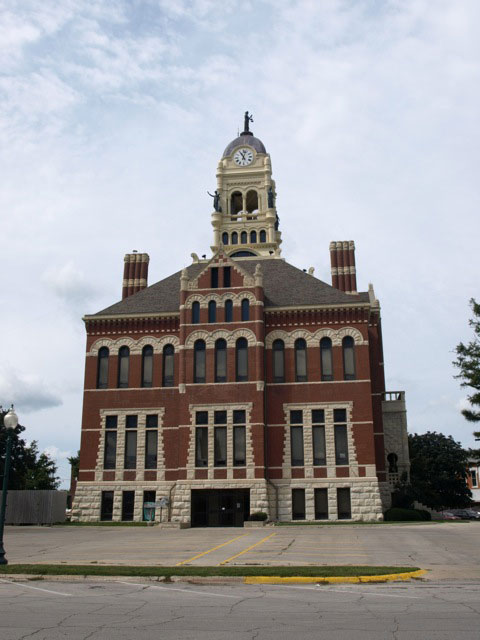 Side view of courthouse shows clocktower with statue on top