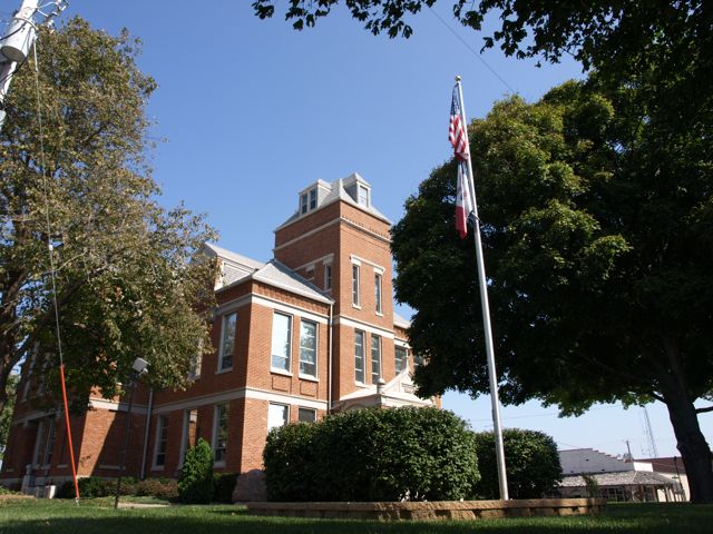 A view of the southwest corner of the courthouse. A flagpole is in the foreground, and the main entrance is hidden behind shrubs.