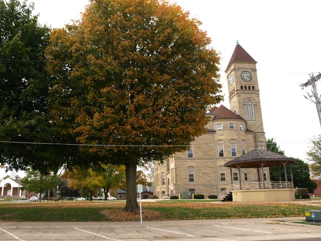 View of east side of courthouse from across the street. Autumn trees, and bandstand on the east lawn.