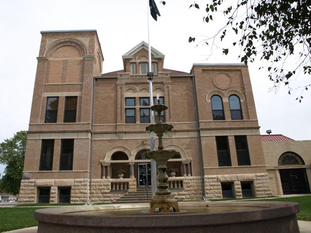 A view of the west side of the courthouse. A fountain is in the foreground, in front of the entrance.