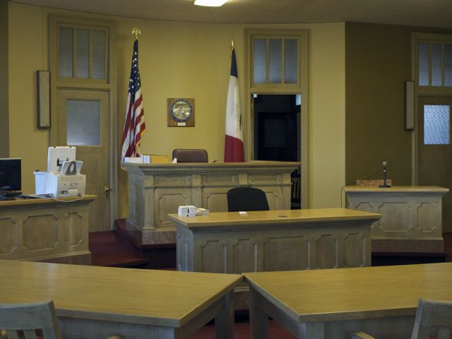 A view of the courtroom, with light colored hand-carved wood
