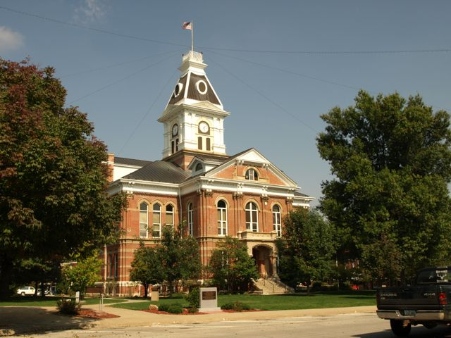 View of the courthouse from the southwest corner, including memorials on the courthouse lawn, the entrance, and the clocktower.
