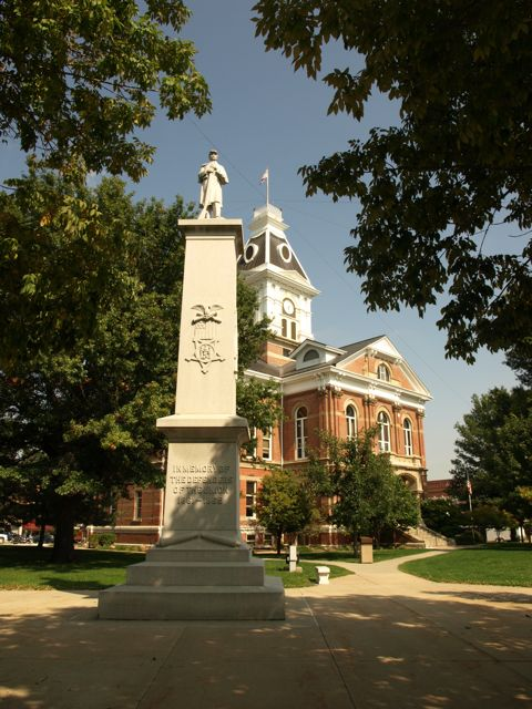 View of the courthouse from the southwest. A civil war monument is in the foreground with a soldier at parade rest.