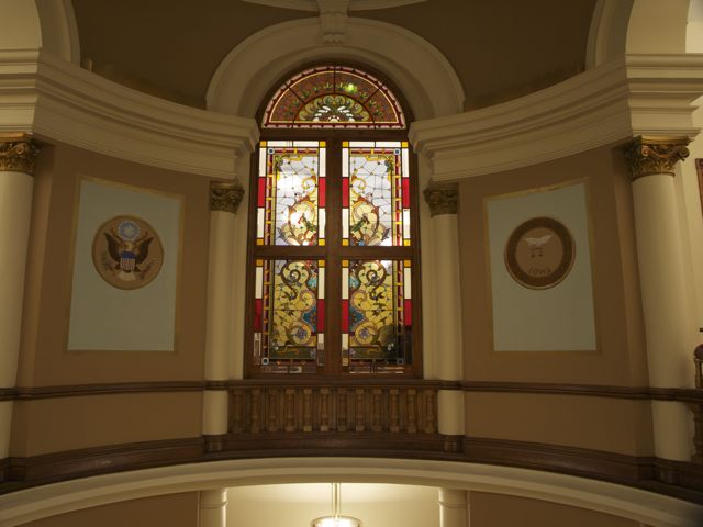View of across the rotunda of the stained glass window outside the courtroom, with replica seals on the rotunda walls