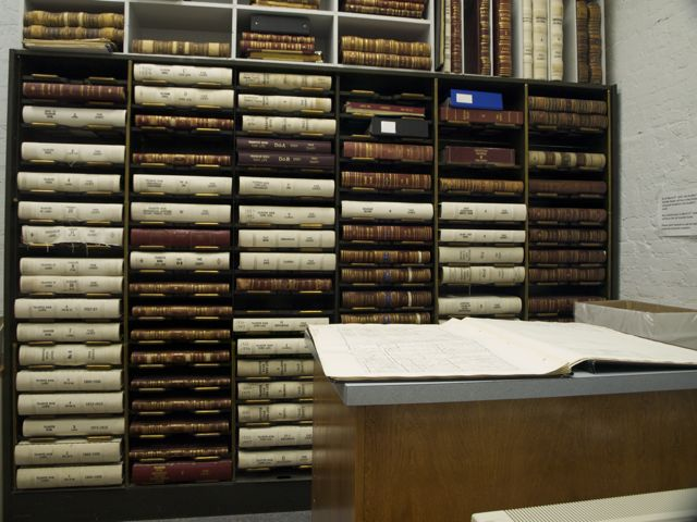 County record books - large leather-bound volumes - stacked horizontally on shelves